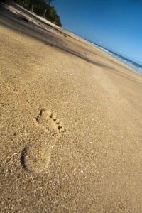 footprints in the sand, a walk along a deseted tropical beach